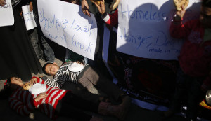 Palestinian children lie on the ground as they take part in a rally to show solidarity with Palestinian refugees in Syria's main refugee camp Yarmouk