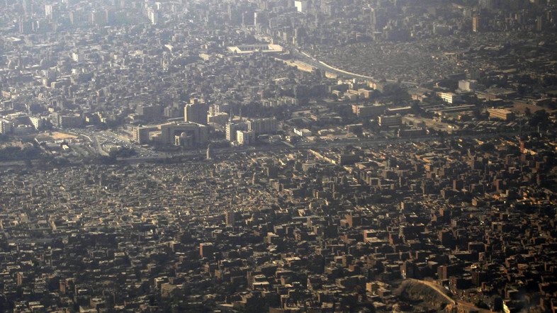 An aerial view of Cairo's traffic and houses is pictured through the window of an airplane