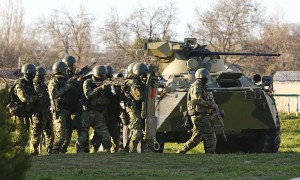 Russian troops take cover behind an armoured vehicle as they take over a Ukrainian airbase in Belbek