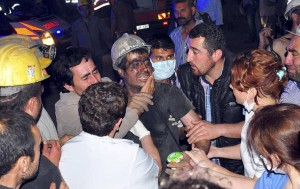 A rescued miner surrounded by relatives, medics and other miners cries after being rescued from a coal mine he was in trapped in Soma, a district in Turkey's western province of Manisa