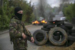 A pro-Russian separatist guards a checkpoint as tyres burn behind him, near the town of Slaviansk