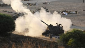 An Israeli tank fires a shell into the Gaza Strip from its position near the enclave on July 23, 2014. Foto: Press Tv