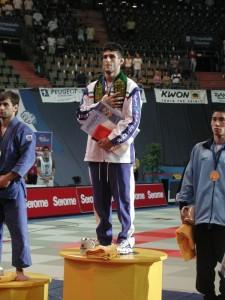 Arsh Miresmaili, Juara Dunia 2003, dengan syal Al-Quds dan tangan memegang Al-Quran,