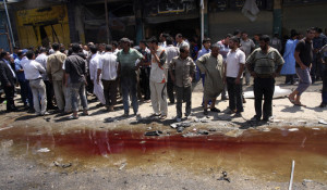 Residents look at a pool of blood after a car bomb attack in Kerbala