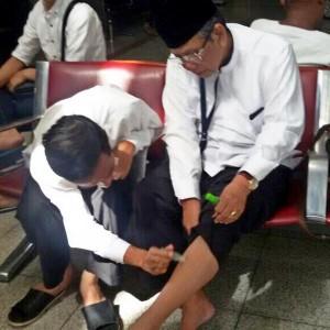 Jokowi sedang mengoleskan balsem cair ke kaki KH Hasyim Muzadi