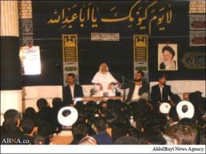 Syaikh Ahmad Yassin menyampaikan ceramahnya di bawah spanduk bertuliskan salam kepada Imam Husain  pada acara pertemuan dengan pelajar asing di Qom, Iran.