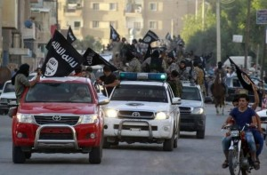 Militant Islamist fighters waving flags, travel in vehicles as they take part in a military parade along streets of Syria's northern Raqqa province