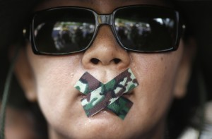 A woman with her mouth taped attends a protest against military rule in Bangkok