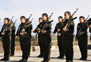 Kurdish female fighters of the Kurdish People's Protection Units hold their weapons at a military camp in Malikiya