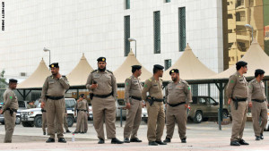 Saudi policemen stand guard in front of