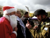 Foto:A Palestinian protester dressed in a Santa Claus costume argues with a member of the IOF during a demonstration against the illegal Israeli settlements and demanding for free movement for the Palestinians during the Christmas period near a checkpoint in the occupied West Bank biblical city of Bethlehem on December 23, 2014. AFP / Musa al-Shaer