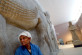 Seventy-seven-year-old Iraqi guard Abed Atiya al-Shemari leans on an Assyrian relief at Baghdad's National Museum June 26, 2004. Al-Shemari has worked in the museum for the past sixty years, and was at work in 2003 when he was forced to flee looters after the fall of [Saddam Hussein's] regime. The archaeological museum has started packing away the fabulous treasures of Assyria, Sumeria and Babylon as a precautionary move to protect them from further lootings. - RTXMPZU