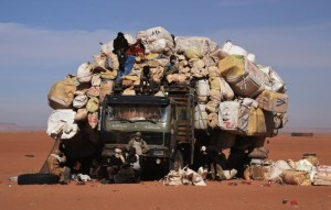 People sit near a fully loaded in Madama near the border with Lybia on January 1, 2015. AFP/Dominique Faget