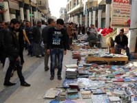 Iraqis look at books on al-Mutanabi Street (AP Photo/Karim Kadim)