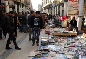 Iraqis look at books on al-Mutanabi Street (AP Photo/Karim Kadim)