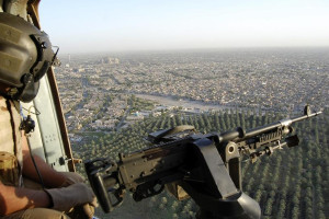A member of the Iraqi Air Force looks out of a military helicopter at an aerial view of Baghdad