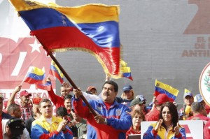 Venezuela's President Nicolas Maduro (C) waves a Venezuelan flag during a rally to commemorate the 26th anniversary of the social uprising known as 'Caracazo', which Venezuela's late President Hugo Chavez said marked the start of his revolution