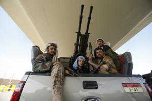Houthi fighters ride a military truck outside the Presidential Palace in Sanaa