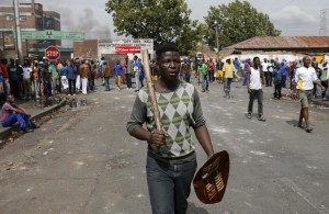 A local gestures as he holds a stick and a shield outside a hostel during anti-immigrant related violence in Johannesburg