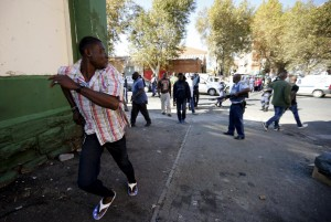 African immigrant runs as a police officer holds a gun to disperse them in Johannesburg