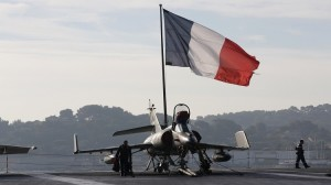Flight deck crew work around a Super Etendard fighter jet as a French flag flies aboard the French nuclear-powered aircraft carrier Charles de Gaulle before its departure from the naval base of Toulon