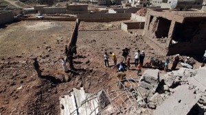 Yemeni men gather around a crater caused by a Saudi airstrike in the capital, Sana'a, November 29, 2015. (AFP)