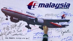 A woman writes a message on a board in Kuala Lumpur