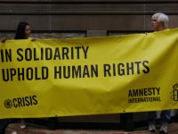 Amnesty International supporters hold a banner in this Feb. 12, 2011 photo. (Photo by Richard Potts via Flikr)