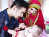 Arabian parents wearing muslim clothes, smiling with their baby boy while sitting in the living room
