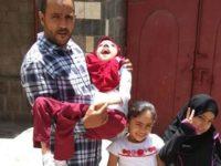 Najeeb al-Omari bersama dengan putrinya Shalma (digendong), Salma, dan Lamia di depan rumah mereka di Yaman.