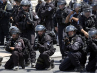 Israeli police officers aim their weapons as Palestinians protest outside Jerusalem's Old City Friday, July 28, 2017. Israeli police were on high alert Friday ahead of Muslim prayers at a major Jerusalem shrine at the center of recent tensions. (AP Photo/Ariel Schalit)