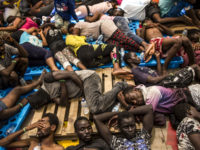 In this photo taken on Wednesday, Aug. 10, 2016, migrants from Nigeria and Ivory Coast rest on a vessel after being rescued by a Migrant Offshore Aid Station, MOAS team in the central Mediterranean Sea, close to the Libyan territorial waters. (AP Photo/Manu Brabo)