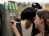 "Israeli girls write messages in Hebrew on shells ready to be fire by mobile artillery unit toward Hezbollah targets in southern Lebanon 17 July 2006, at a military staging area along the northern Israeli border with Lebanon.  Prime Minister Ehud Olmert vowed today to continue Israel's punishing twin offensive against the ""terrorists"" of Hezbollah and Hamas, declaring his country was facing a ""moment of truth"".  At least 47 people were killed in Israeli strikes in Lebanon today and 10 more bodies found, pushing the death toll from the Israeli offensive to more than 200 over the past six days. The overall toll now comprises 195 civilians and 12 soldiers killed in Lebanon since 12 July, medics and police said. Nine of the 12 soldiers were killed today. More than 440 people have been wounded. AFP PHOTO/PEDRO UGARTE (Photo credit should read PEDRO UGARTE/AFP/Getty Images) (Newscom TagID: afplive254935.jpg) [Photo via Newscom]"