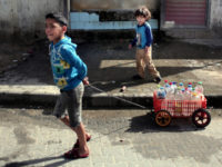 In this Saturday, April 16, 2016 photo, A Palestinian boy uses a homemade wagon made from a plastic crate to wheel bottles full of drinking water in front of a water supply station in Khan Younis refugee camp, southern Gaza Strip. Poor sewage treatment is a feature of life in Gaza, a result of the rapidly expanding population, an infrastructure damaged during wars with Israel and a chronic shortage of electricity to run the wastewater plants that still function. (AP Photo/Khalil Hamra)