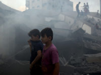 Palestinians inspect the damaged building of Said al-Mis'hal cultural center after it was hit bombed by an Israeli airstrike in Gaza City, Thursday, Aug. 9, 2018.  The Palestinian Health Ministry says several bystanders were wounded in Thursday evening's airstrike in the Shati refugee camp. (AP Photo/Khalil Hamra)