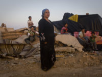 A Bedouin woman watches as Israeli bulldozers destroy an improvised living structure in the village of Al Araqib, Negev, August 10, 2010. This was the second demolition in less than a month. On July 27, 30 homes, infrastructure and animal pens were demolished by Israeli authorities.  Residents of unrecognised villages are unable to get building permits for their houses.