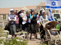 In this June 4, 2012 file photo, Jewish settlers march during a demonstration against the proposed decision to evacuate a West Bank outpost in the Ulpana neighborhood, in the West Bank settlement of Beit El near the Palestinians city of Ramallah. Opposition politicians politicians have singled out the World Zionist Organization's Settlement Division, Israel's main subcontractor in the settlements, for its inflated budgets and little accountability. Israel funneled eight times more funding to the group this year than what was initially approved in the national budget. (AP Photo/Ariel Schalit, File)