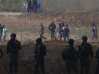 Israeli soldiers are positioned as Palestinian protesters arrive during a protest along the Israel Gaza border in Israel, Friday, Oct. 19, 2018. (AP Photo/Ariel Schalit)