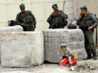 Israeli border police officers stand guard as a Jewish settler boy plays near a disputed house in the West Bank city of Hebron where Israeli settlers pitched a Sukkah, or makeshift hut marking a Jewish harvest festival, outside a contested house in the West Bank city of Hebron in a new claim to ownership.