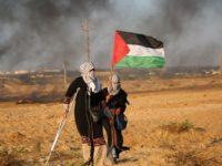 Demonstran Palestina membawa sebuah bendera nasional saat aksi protes menuntut berakhirnya blokade Israel di jalur Gaza.