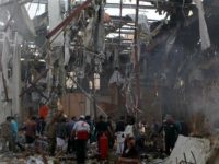 Warga Yaman dan tim penyelamat berkumpul di bangunan yang rusak akibat serangan udara koalisi Saudi di Sana'a. (Photo by AFP)